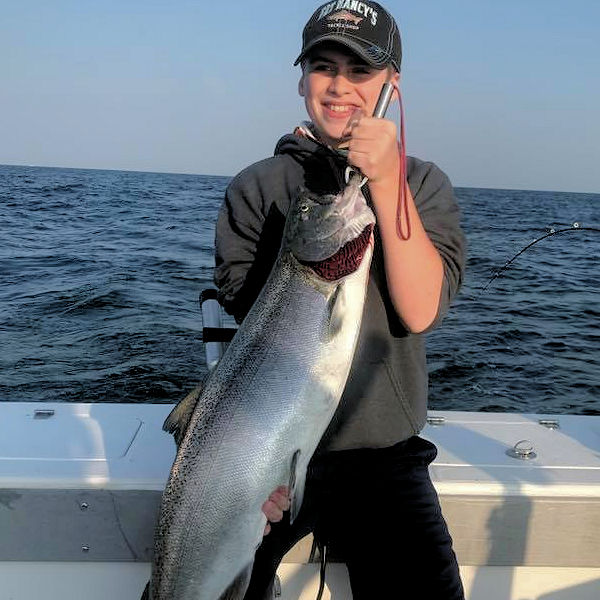 Young man holding up another awesome Lake Ontario king salmon.