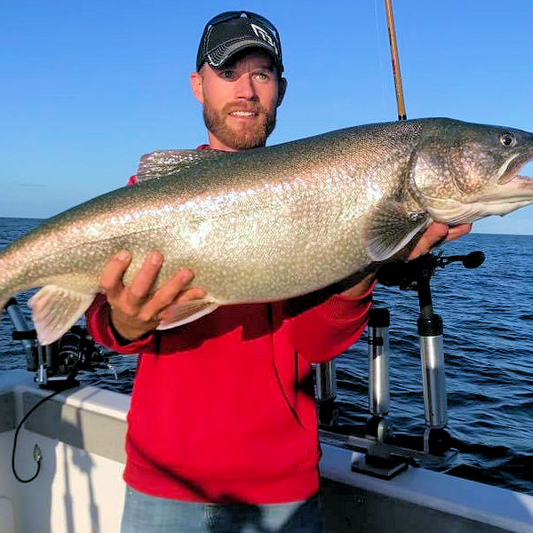 Great picture of Lake Ontario angler holding a large lake trout.