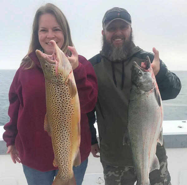 Lake Ontario couple holding up nice brown trout and king salmon.